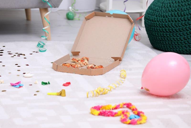 Pizzaask med rester på smutsigt lägenhetgolv arkivfoto