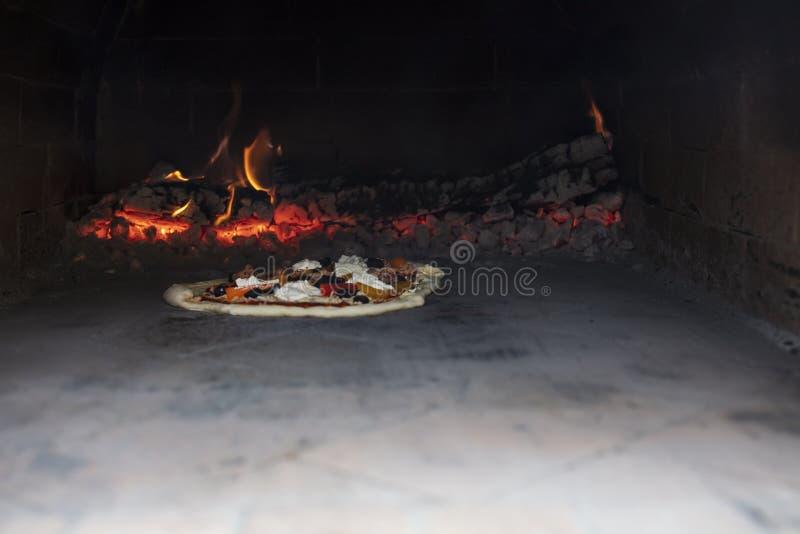 Pizzabacken in einem Ofen im Freien mit hölzernem Burning lizenzfreies stockfoto