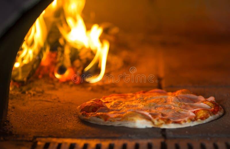 Pizzabakning i traditionell stenugn arkivbilder