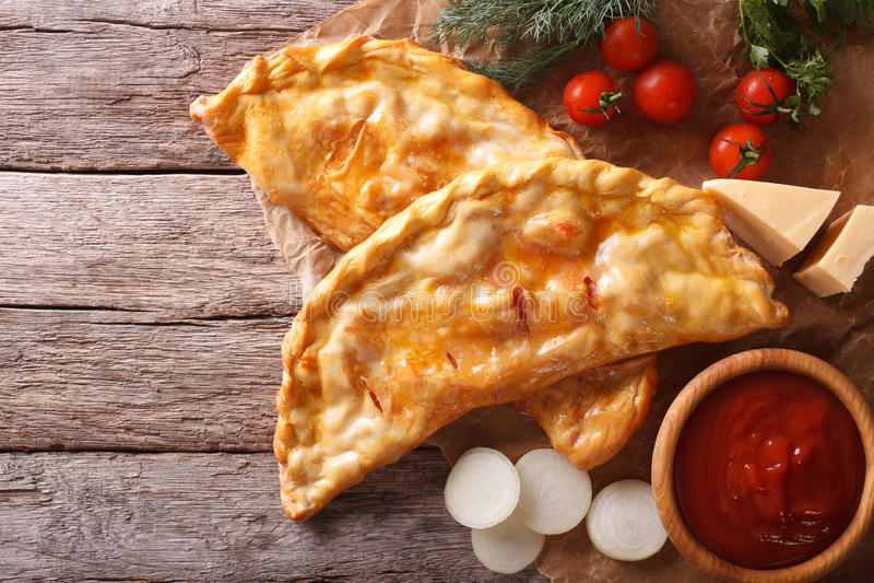 Pizzacalzone op een document en ingrediënten horizontale hoogste mening stock foto's