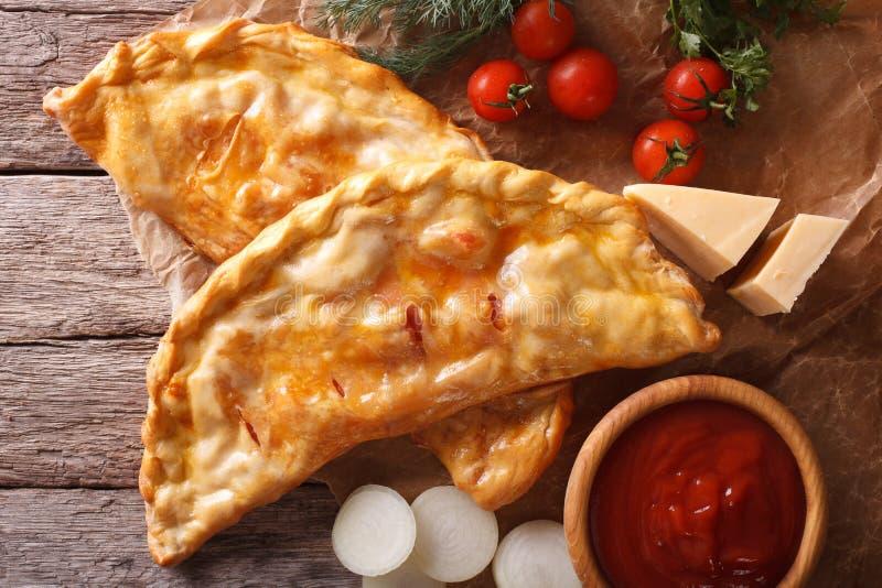 Pizzacalzonecloseup på ett papper och ingredienser horisontalöverkant arkivbild