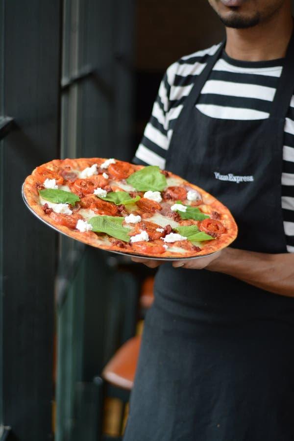 PizzaExpress Pizzaiolo con un ossequio sottile della pizza della crosta - cucina italiana immagini stock libere da diritti