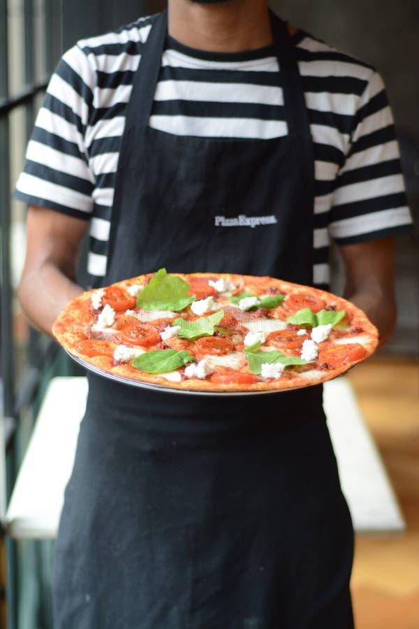 PizzaExpress Pizzaiolo con una invitación fina de la pizza de la corteza - cocina italiana imagen de archivo libre de regalías