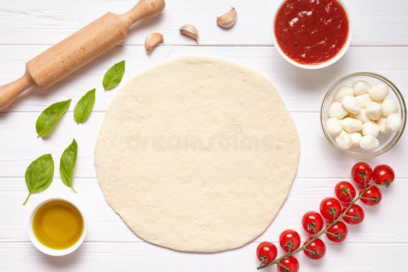 Pizzaförberedelse Stekheta ingredienser på köksbordet: rullande deg, mozzarella, tomatsås, basilika, olivolja fotografering för bildbyråer