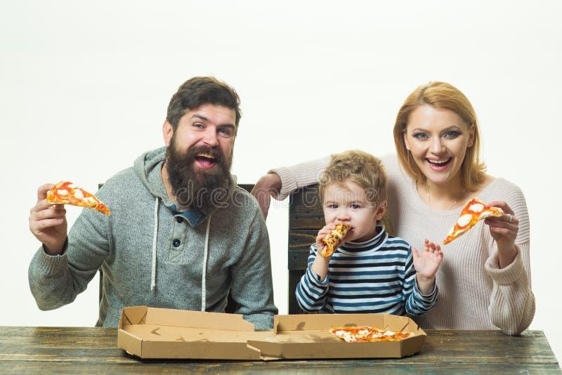 Pizzafamilie Moeder, vader en kind, een kleine zoon met ouders die pizza eten Familiediner met mamma en papa italiaans royalty-vrije stock fotografie