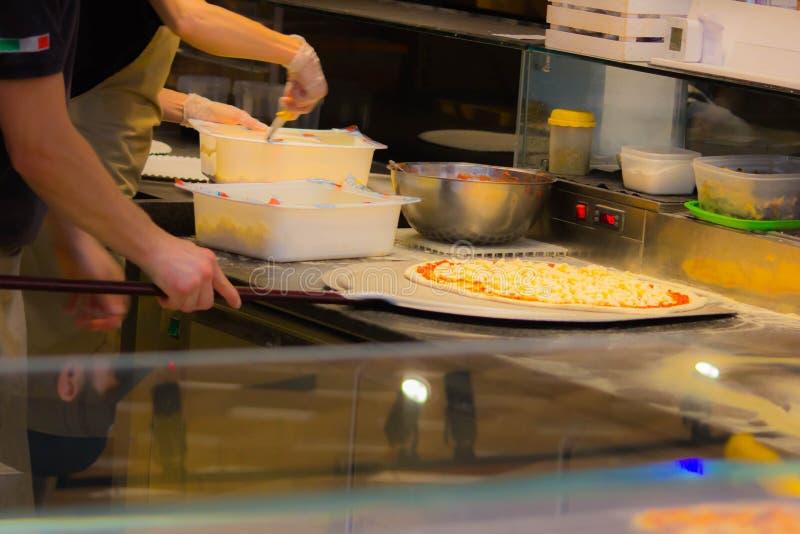 Pizzahersteller beim Vorbereiten, eine Pizza zu backen noch heute in den Pizzerias werden die Holzofen bevorzugt stockfotografie