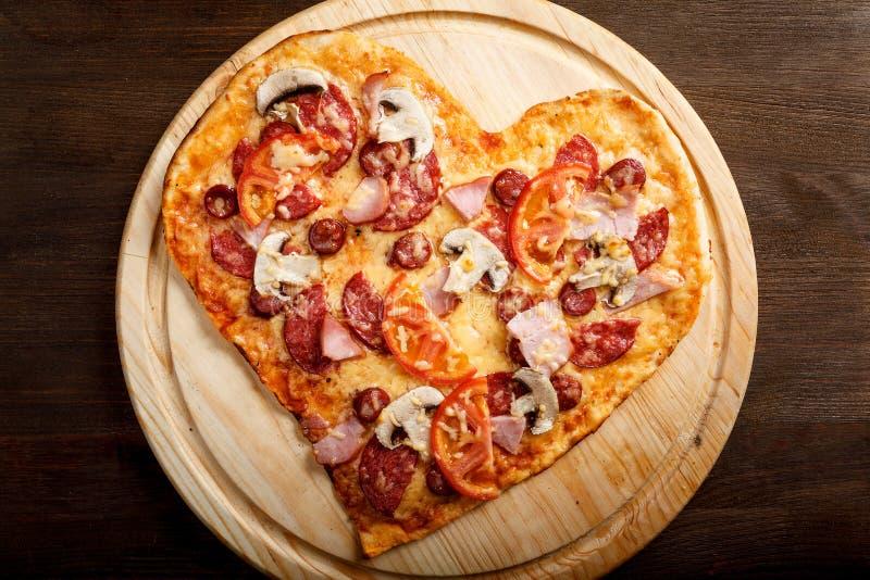 Pizzaherzform auf Draufsicht des dunklen hölzernen Hintergrundes stockfoto