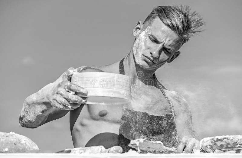 Pizzaiolo概念 贝克与面粉和筛子,揉的面团一起使用 人肌肉面包师或厨师通过过滤面粉 库存图片