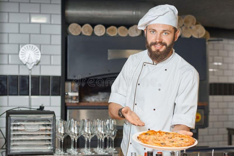 Pizzaiolo feliz que demonstra a pizza deliciosa cozida fresca fotos de stock royalty free