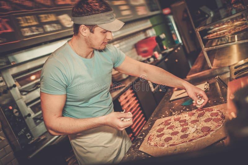 Pizzaiolo hermoso que hace la pizza en la cocina fotos de archivo libres de regalías