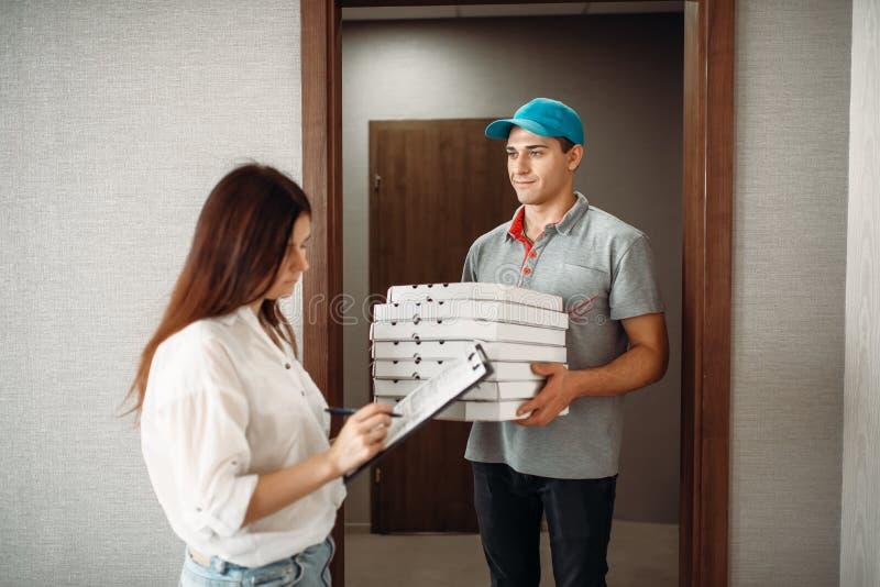 Pizzaleveranspojken tar en spets från kund arkivbilder