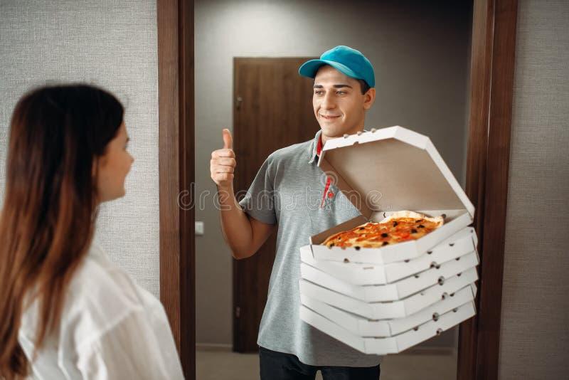 Pizzaleveranspojken visar kunden för tummar upp till royaltyfri foto