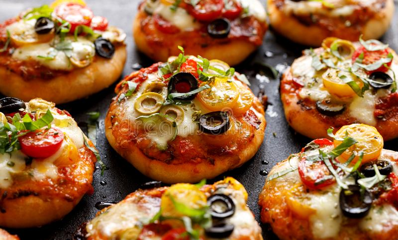 Pizzas pequenas do vegetariano com os vários tipos da adição dos vegetais, do mozzarella e da manjericão fresca imagens de stock royalty free
