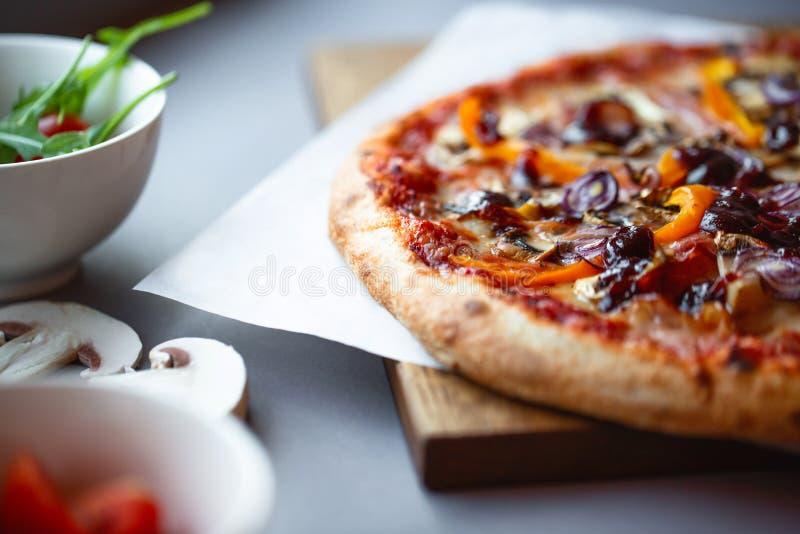 Pizzasamenstelling op houten lijst met grijze hand als achtergrond royalty-vrije stock afbeeldingen