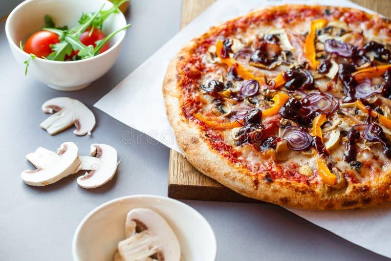 Pizzasamenstelling op houten lijst met grijze hand als achtergrond stock afbeeldingen