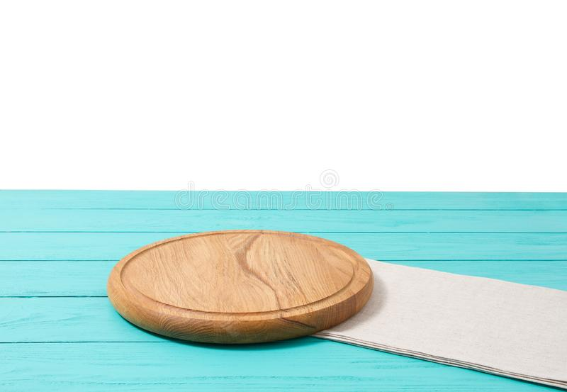 Pizzaskärbräda och bordduk för runt trä på den blåa trätabellen som isoleras på vit bakgrund Utrymme för bästa sikt som och kopie arkivfoto