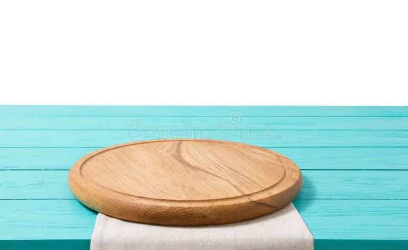 Pizzaskärbräda och bordduk för runt trä på den blåa trätabellen som isoleras på vit bakgrund Utrymme för bästa sikt som och kopie royaltyfria bilder