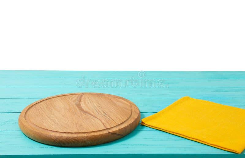 Pizzaskärbräda och bordduk för runt trä på den blåa trätabellen som isoleras på vit bakgrund Utrymme för bästa sikt som och kopie arkivbilder