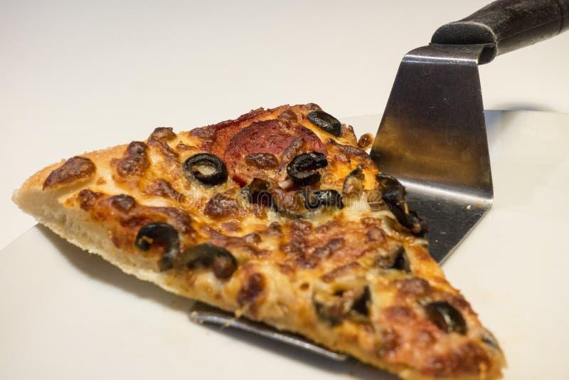 Pizzaskivaportion med spateln på den vita plattan arkivbild