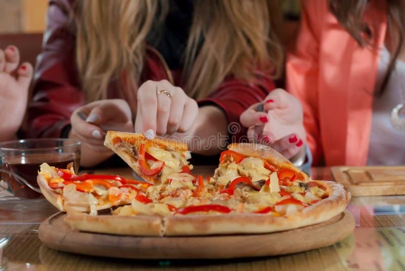 Pizzatid- och flickavänner som har god tid royaltyfria bilder