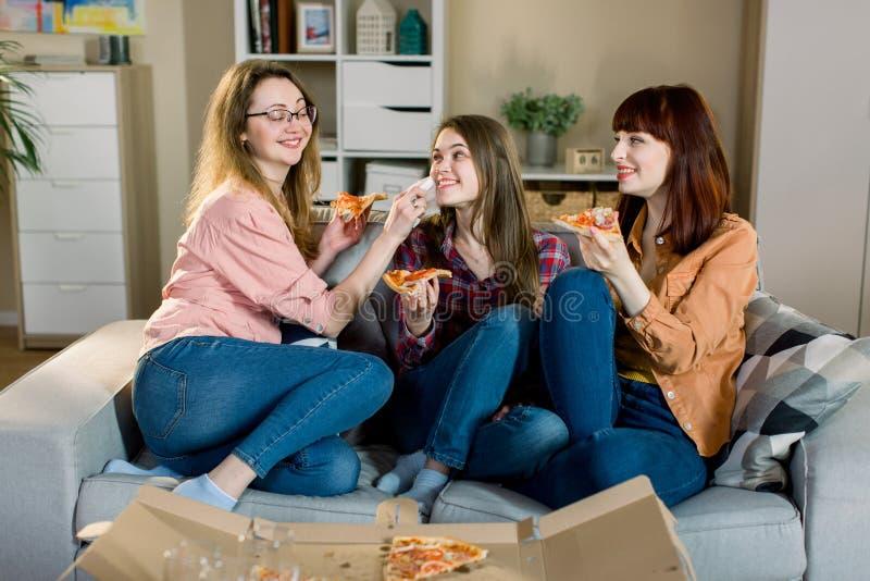 Pizzatid Tre nätta le kvinnor som tillsammans äter pizza och att ha gyckel i den hem- matsalen Frienship mat royaltyfria foton