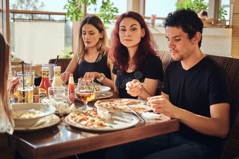 Pizzatid Unga vänner som tycker om pizza och sallad i ett utomhus- kafé arkivfoton