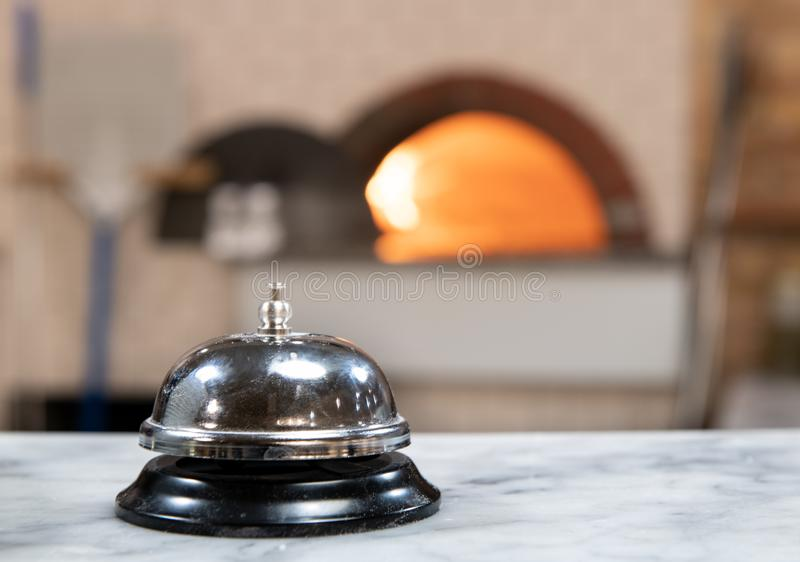 Pizzeria service bell close up wood fire oven in background. Close up of service bell in pizzeria worktop, defocused background with wood oven and red fire royalty free stock photo
