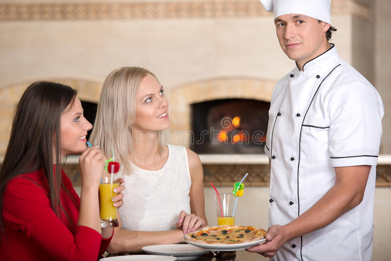 Pizzeria. Waitress is giving pizza to a smiling young women at the pizzeria. He is looking on the camera royalty free stock photos