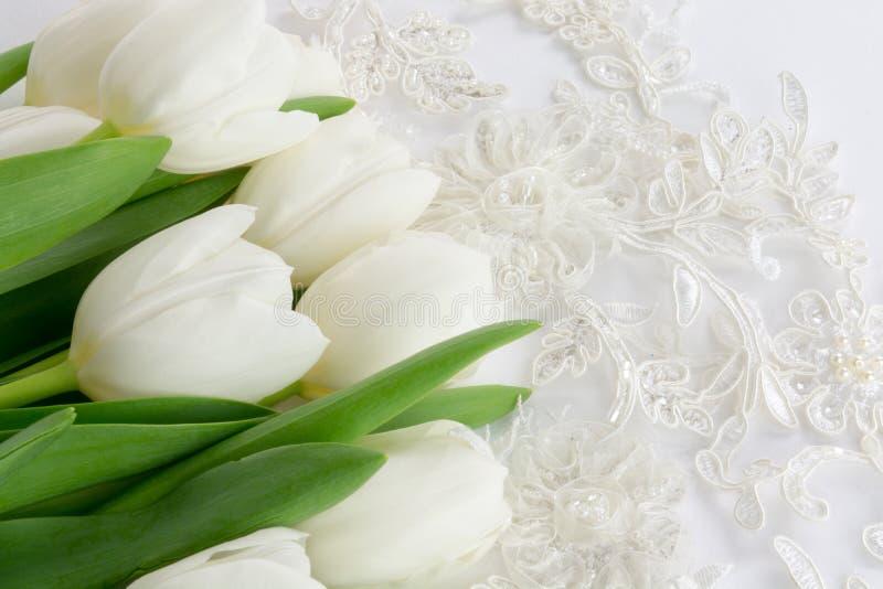 Pizzo di nozze e tulipani bianchi su un fondo bianco immagini stock libere da diritti