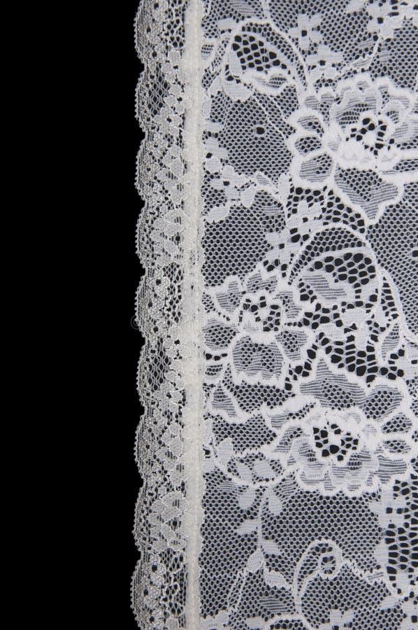 Pizzo floreale bianco sul nero fotografie stock