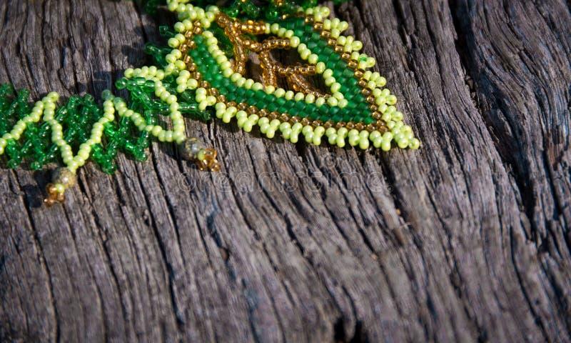 Pizzo verde del perla-lavoro su un fondo di legno immagini stock