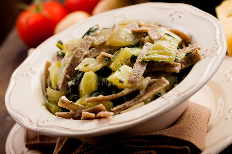Pizzoccheri. North Italian Regional pasta dish called pizzoccheri on wooden table royalty free stock images