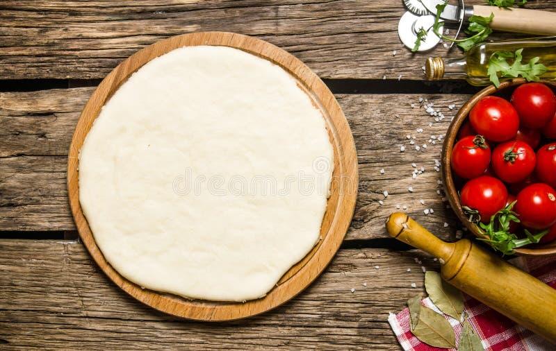 Pizzy ciasto z pomidorami i ziele z toczną szpilką, zdjęcia stock