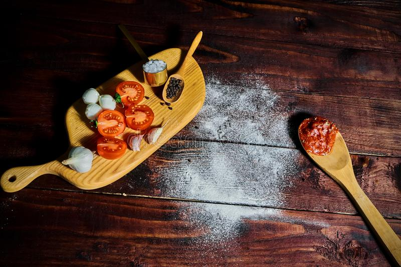 Pizzy ciasto z pomidorami, oliwą z oliwek, zielonym basilem i mozzarellą na drewnianym tle, obrazy stock