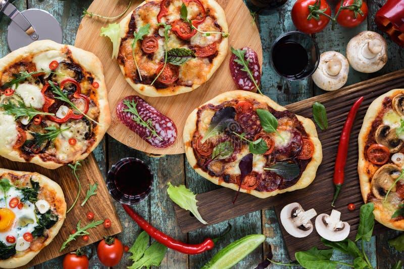 Pizzy i wina przyjęcie Domowej roboty nieociosane pizze i surowi składniki fotografia royalty free