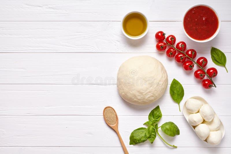 Pizzy margherita przygotowania tradycyjny przepis z wypiekowymi ingridients: surowy ciasto, czereśniowi pomidory, basil, pomidoro obrazy stock
