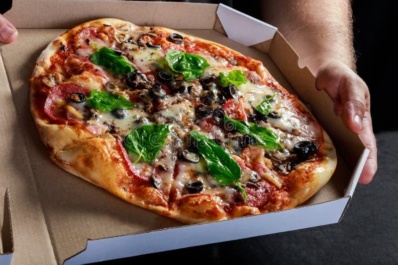 Pizzy pudełkowaty doręczeniowy pojęcie Otwarty pudełko z gorący smakowity włoch pokrajać pizzą z oliwkami, basil, pomidor, ono ro obrazy stock