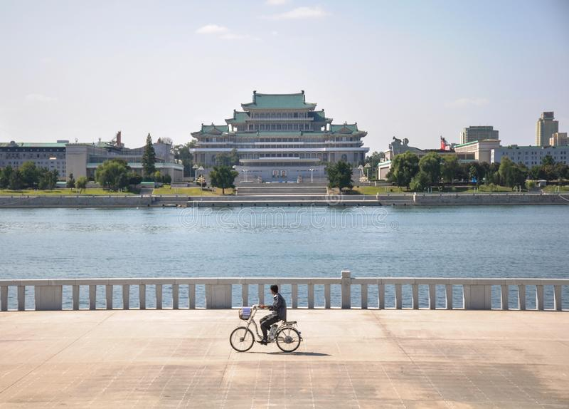 09/09/2018: Pjöngjang, Norden-Korea: ein einsamer Radfahrer, der Kim Il Sung Palace führt stockbild