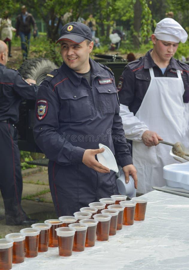 PJATIGORSK, RUSSIA - 9 MAGGIO 2017: L'impiegato della polizia distribuisce la cucina bianca mobile dell'alimento e del tè immagine stock libera da diritti