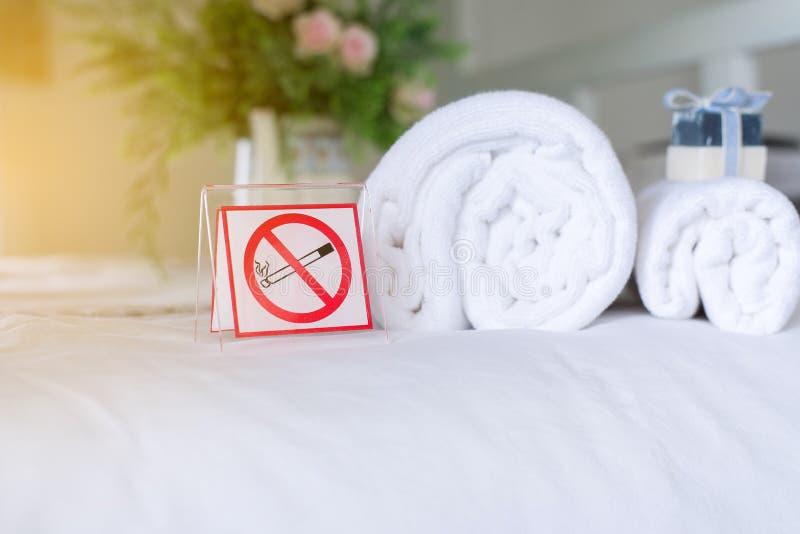 Plástico branco dos sinais não fumadores na cama no hotel imagem de stock
