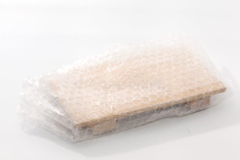 Plástico de burbujas blanco que taja la madera fotografía de archivo