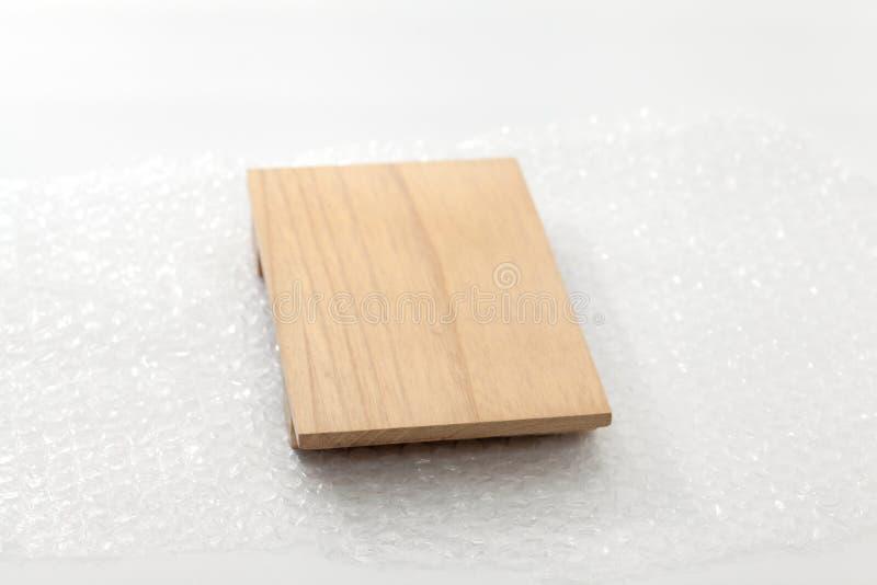 Plástico de burbujas blanco que taja la madera fotos de archivo