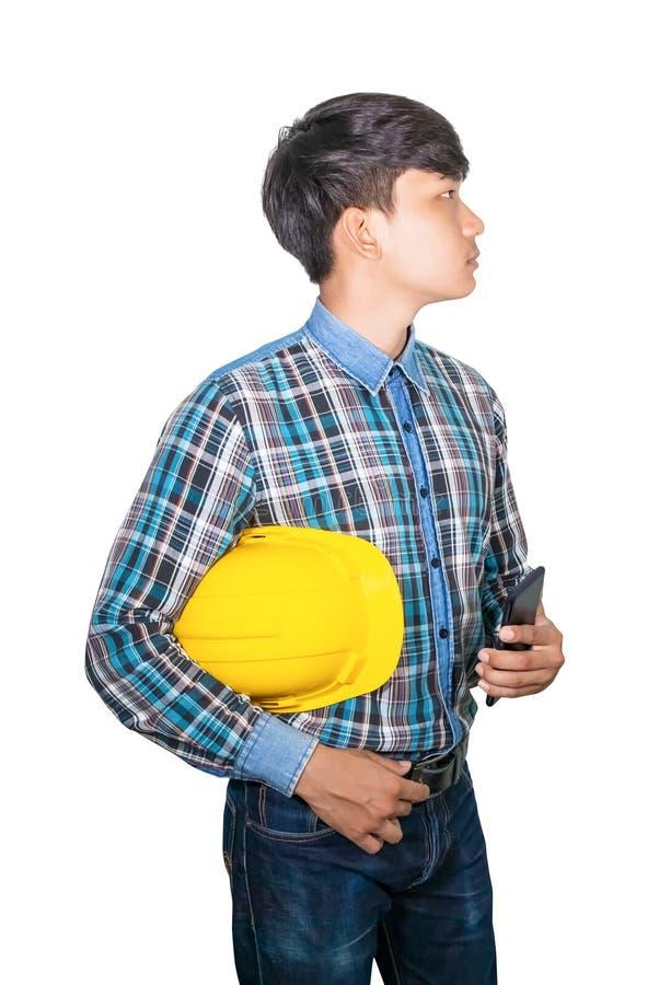 Plástico e telefone celular amarelos do capacete de segurança da posse do coordenador do homem de negócios no fundo branco fotos de stock