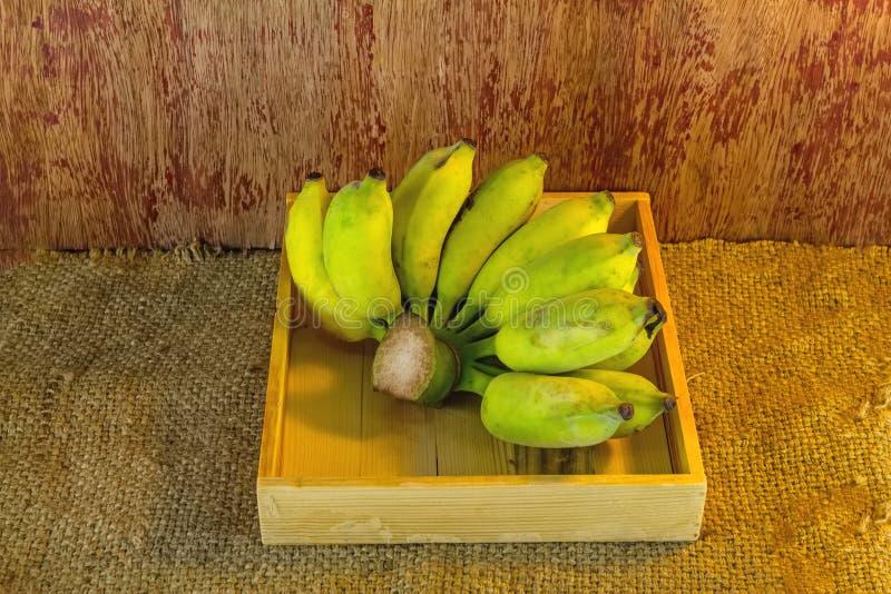 Plátano verde en una caja de madera, en fondo del sisal del saco imagen de archivo