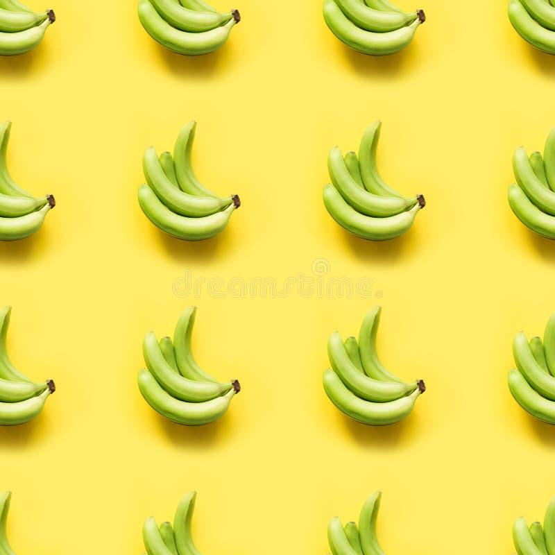 Plátano verde fresco dulce en fondo amarillo en colores pastel dinámico Visi?n superior Modelo incons?til fotos de archivo