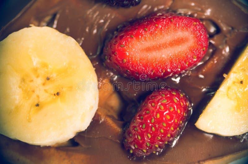 Plátano y fresa en la salsa de chocolate desde arriba del ángulo imagenes de archivo
