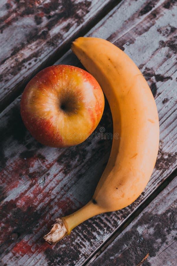 Plátano y manzana en la tabla vieja fotografía de archivo libre de regalías
