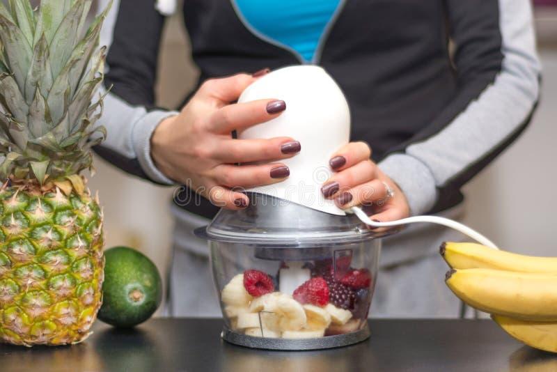 Plátano, zarzamora, arándanos y frambuesas de mezcla de la mujer en licuadora imagen de archivo libre de regalías
