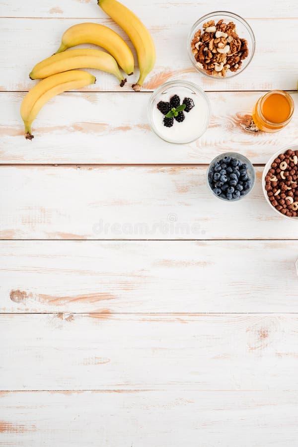 Plátanos, bayas, nueces y miel en fondo de madera fotografía de archivo libre de regalías
