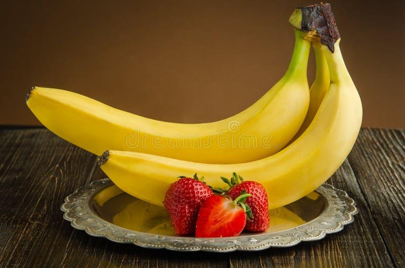 Plátanos con las fresas en una placa del vintage imagenes de archivo